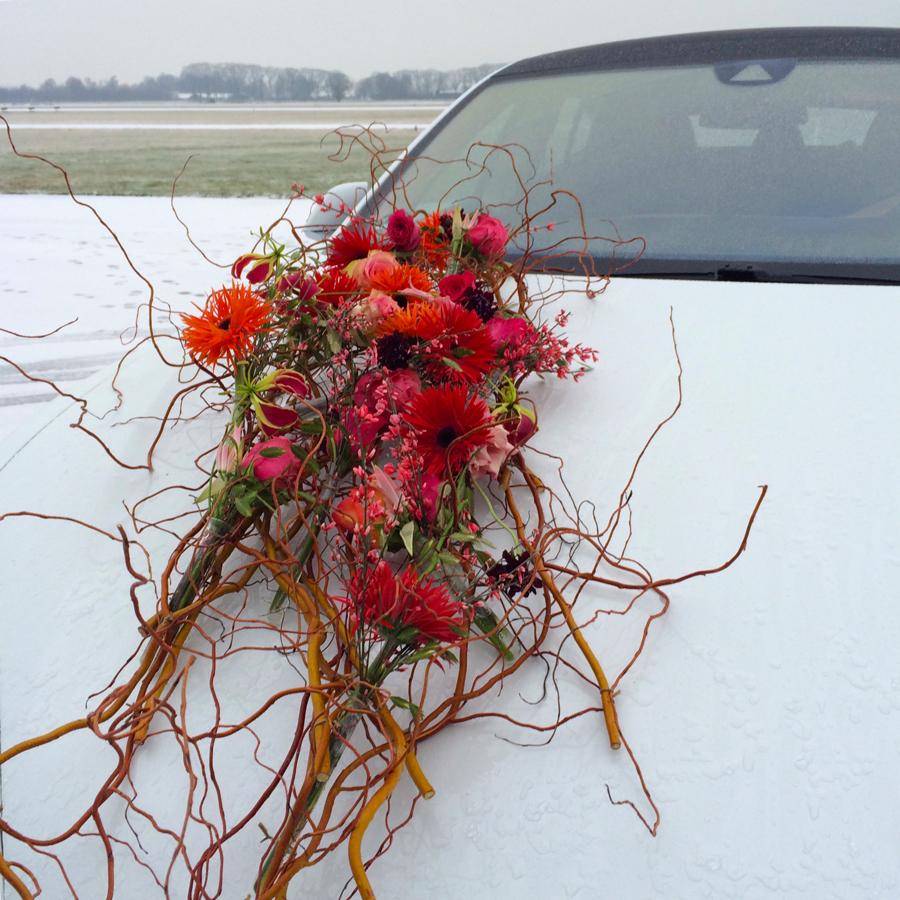 Autocorsage in wintersfeer met takken en gerbera's