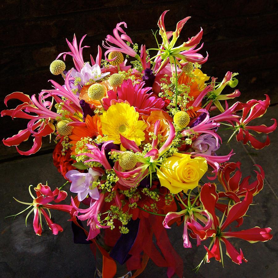 Felgekleurd bruidsboeket waarin gele gerbera's en rozen