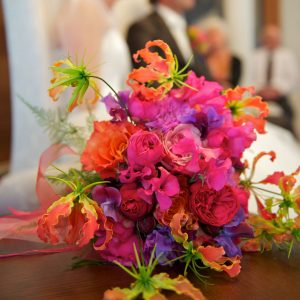 Oranje rozen, knalrose pioenrozen en paarse latyrus in een spetterend bruidsboeket