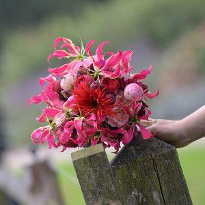 Knallend rose-rood bruidsboeket met gloriosa, pioenrozen en gerbera