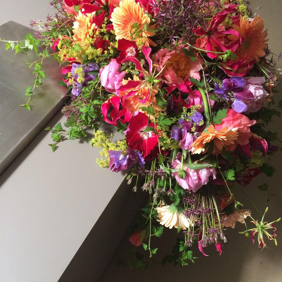 Bloemen bij een afscheid   Kistbedekking veelkleurig in druppelvorm