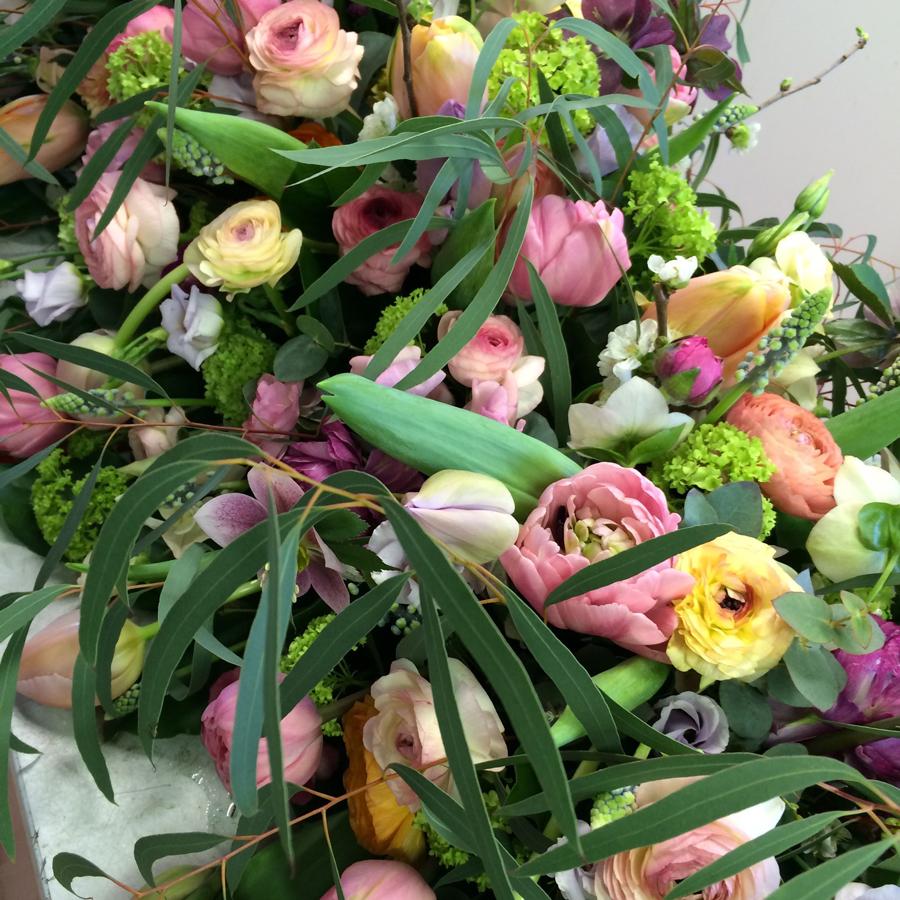 Bloemen bij een afscheid   Rouwarrangement in lentebloemen