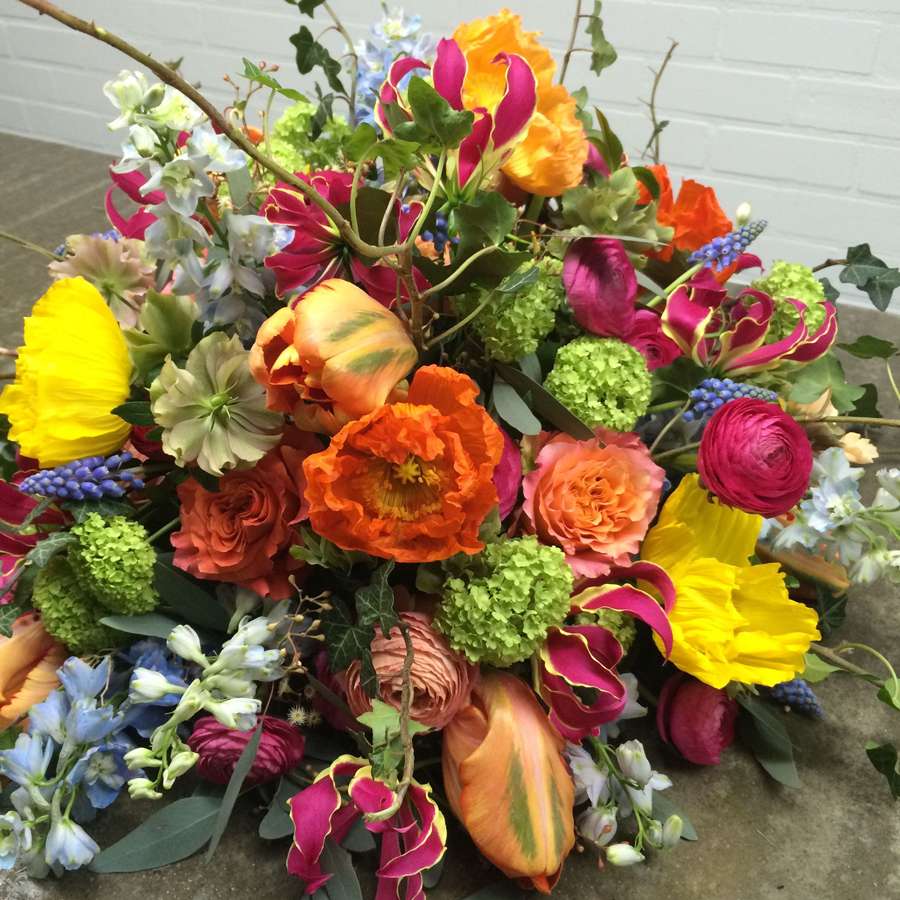 Bloemen bij een afscheid   Rouwarrangement veelkleurig