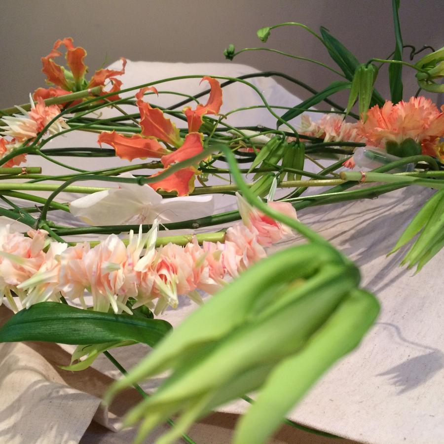 Bloemen bij een afscheid   Rouwarrangement lijkwade oranje gloriosa en zachtgroen
